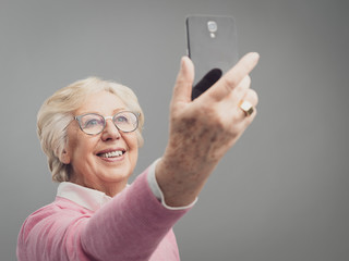 Happy senior woman taking selfies with her smartphone