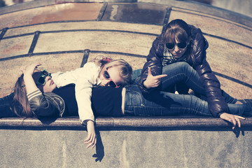 Group of happy teen girls lying on parapet