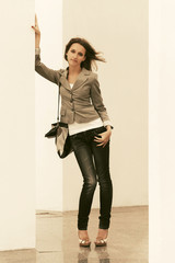 Happy young fashion woman with handbag leaning on the wall