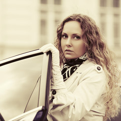 Young fashion woman in white trench coat outside her car