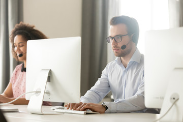 Call center agent in headset using computer in open space