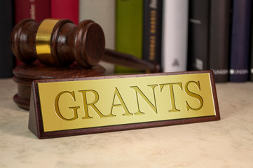Golden sign with gavel and law books on a desk with grants