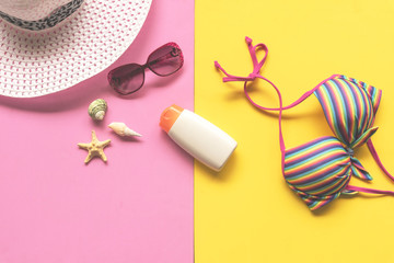 Summer Fashion woman swimsuit Bikini, camera, starfish, sunblock, sun glasses, hat. Travel in the holiday pastel background.  Summer Concept.