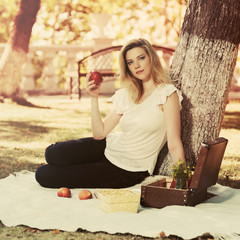 Young fashion blonde woman with apple in city park