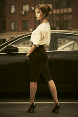 Young fashion business woman in white shirt next to her car