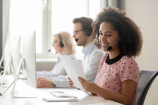 Smiling african woman call center operator wearing headset reading papers