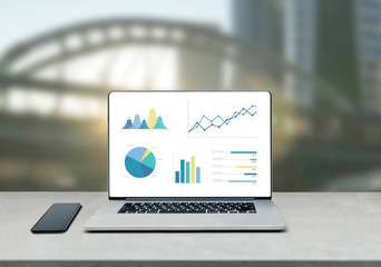 laptop showing chart and graph and mobile phone on table against beautiful  modern business building background, digital marketing report