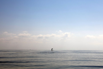 A man paddles on a stand-up board on a beach near the village of Pervolia