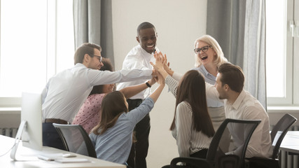 Happy diverse employees business team engaged in teambuilding giving high-five Wall mural