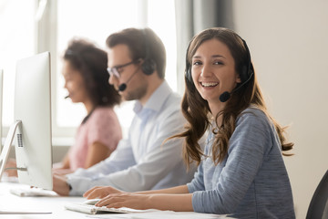 Happy businesswoman call center agent looking at camera at workplace Wall mural