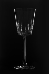 Crystal empty wineglass on the black background