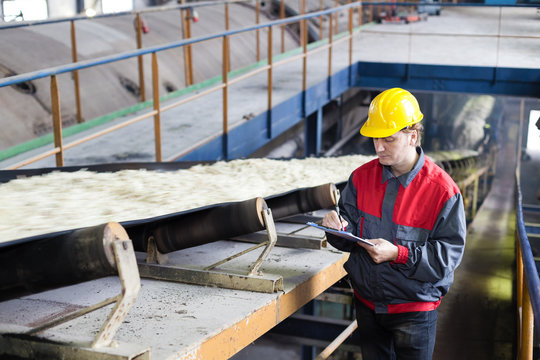 Transport of sugar on the production line, worker writes the quality information