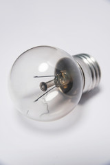 Incandescent lamp. Artificial light source. Glass bulb on white background. Metal base. Electric lighting device.