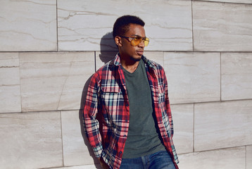 Wall Mural - Stylish african man wearing red plaid shirt, looking away, guy posing on city street, gray brick wall background