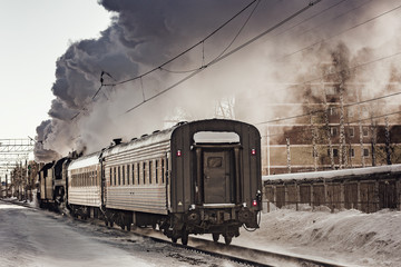 Steam train moves toward at cold winter morning time.