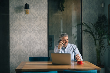 gray haired middle aged man sitting in cafe bar, working on laptop and using smartphone