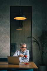 middle aged business man drinking coffee in cafe bar. vertical image with copy space