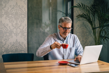 online even on coffee break. senior businessman using laptop and drinking coffee in cafeteria