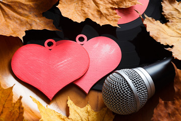 Song for lovers. Nostalgic songs, fallen leaves and melancholy. Concept with vinyl records, microphone and hearts.