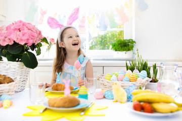 Kids at Easter breakfast. Eggs basket, bunny ears.