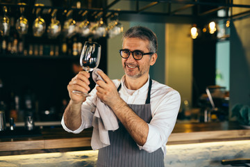he wants everything to be perfect.Middle aged barman polishing the wine glass in cafe bar