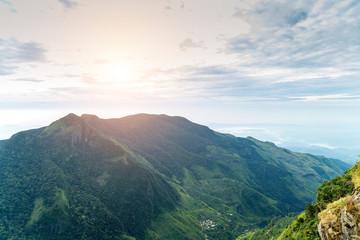 Mountains in summer time sunrise cloud forest Worlds End in Horton Plains National Park Sri Lanka.
