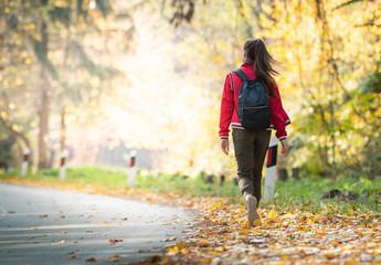 Beautiful girl walking trough forest in autumn season