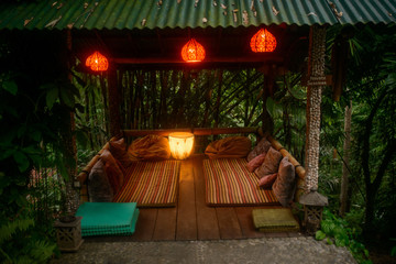 asian launge place witn pillows and red lamps in tropical forest in Bali