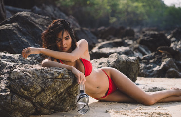 291a190ab8d3 Sexy Asian woman in red colour swimsuit lying down on a stone rock at sea