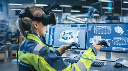 Factory: Female Industrial Engineer Wearing Virtual Reality Headset and Holding Controllers, She Uses VR technology for Industrial Design, Development and Prototyping in CAD Software. Wall mural