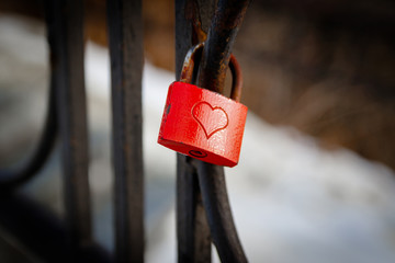 Red love padlock attached to steel fence. Rusty lock with heart shape carved hanging on railing outdoors. Valentines day, unity, memory concepts