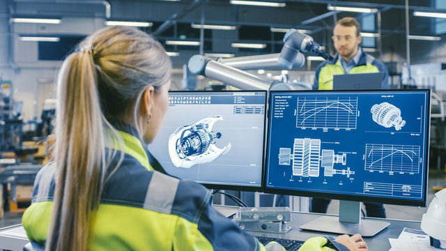 At the Factory: Female Mechanical Engineer Designs 3D Engine on Her Personal Computer. In the Background Male Automation Engineer who Uses Laptop for Programming Robotic Arm.