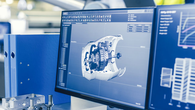 Close-up Shot of the 3D CAD Model of the Engine Shown on Computer Screen. In the Background Manufacturing Factory with People Working.