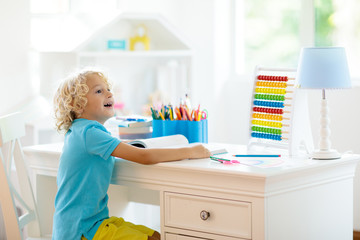 Child drawing rainbow. Kid painting at home. Little girl and boy doing homework after school. Kids desk with abacus in white sunny bedroom. Children study, learn to read and write. Bedroom for student