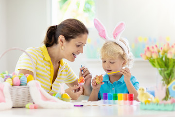 Mother and kids, family coloring Easter eggs.
