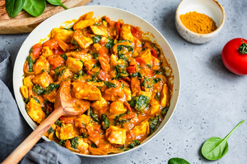 Top view on Bombay chicken curry with spinach, tomato and onion in a white frying pan on a kitchen table. Indian traditional cuisine.