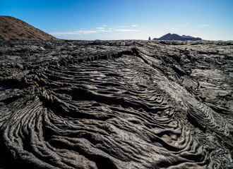 View over Lava field in Sullivan Bay towards Bartolome Island, Santiago or James Island, Galapagos, Ecuador