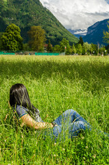 Wall Mural - Girl lies in the grass in city Interlaken, Switzerland