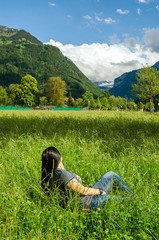 Fototapete - Girl lies in the grass in city Interlaken, Switzerland
