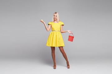 Cheerful beautiful blond young woman in yellow dress tasted a small holiday cupcake. Holds a red box for desserts on white background. Space for text
