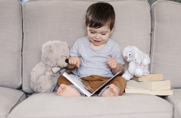Cute adorable happy little baby boy reading book sitting on sofa with soft teddy bear and grey rabbit toy pointing at picture with his finger. Child early development and education concept