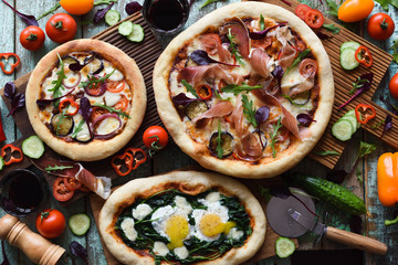 Freshly made yummy pizza party. Flatlay of puffy pizzas with pancetta, aubergines, spinach, eggs, bell pepper and arugula served with raw vegetables and herbs on oak boards