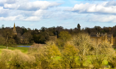 Landscape of Oxfordshire, with distant views of Broughton Castle, its gatehouse, moat  and associated church. Parkland with trees . Spring sunlight on buildings. Blue sky with white clouds. England.