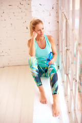 High angle shot of sporty mature woman relaxing after yoga and drinking a bottle of water
