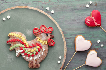 Gingerbreads shaped as a rooster bird and hearts on textured wood