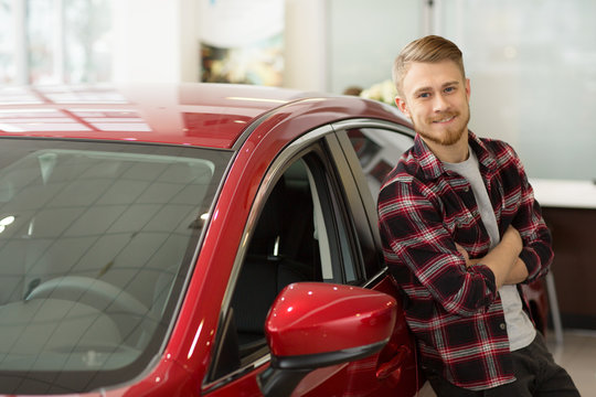 Happy handsome man buying a new car at the dealership