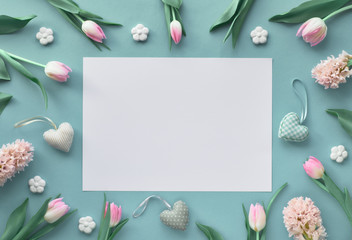 Springtime blue  background with pink tulips, hyacinth, ceramic flowers and decorative hearts, text space