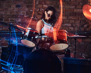Beautiful girl musician in sunglasses holding the sticks sitting behind the drum set against a brick wall. Perform in a night club