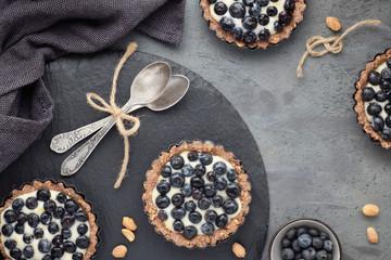 Top view on wholegrain blueberry tarts with vanilla cream on dark