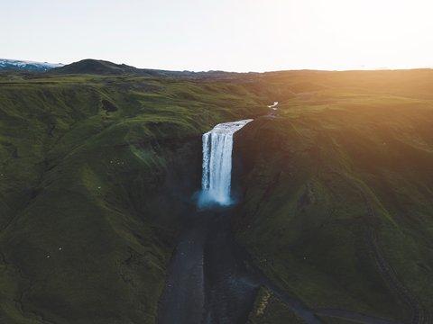 waterfalls near green trees during sunset
